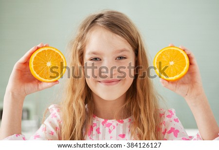 Cheerful girl with orange at home. Child with fruit