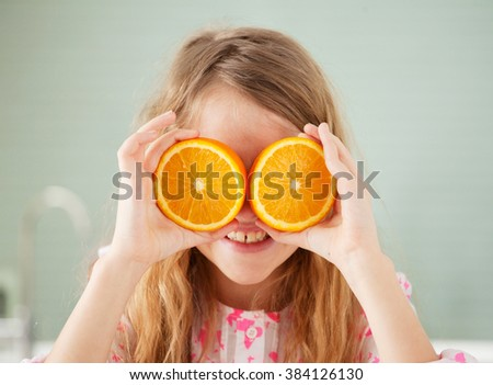 Cheerful girl with orange at home. Child with fruit - stock photo