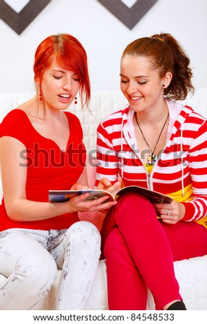 Cheerful girlfriends sitting on sofa at home and looking fashion magazine - stock photo