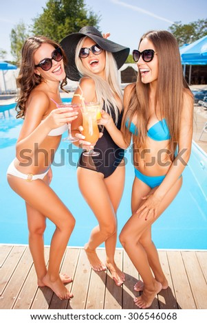 Cheerful girls are resting near a swimming pool. They are drinking cocktails and laughing. The friends are spending time together with pleasure - stock photo
