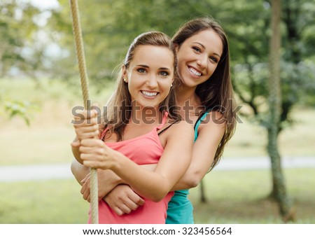 Cheerful girls at the park hugging and holding a rope, friendship and leisure concept - stock photo