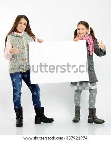 cheerful girls holding blank board - stock photo