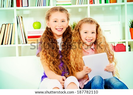 Cheerful girls sisters having a rest at home with a digital tablet. - stock photo