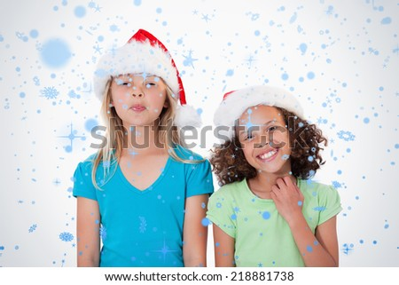 Cheerful girls with Christmas hats against snow falling - stock photo