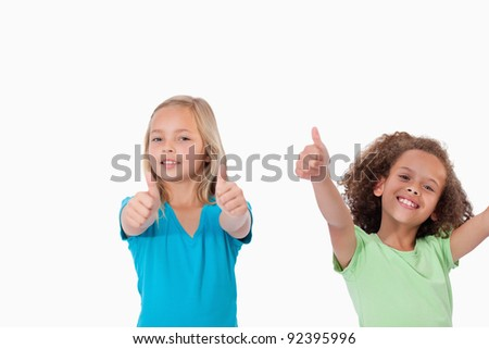 Cheerful girls with the thumbs up against a white background