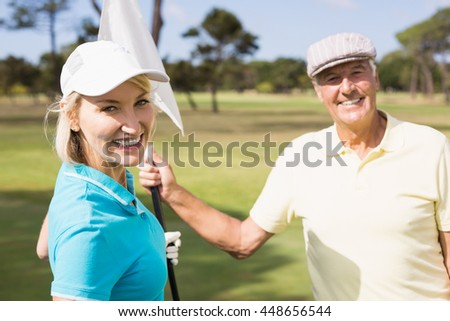 Cheerful golfer couple holding white flag while standing on field - stock photo