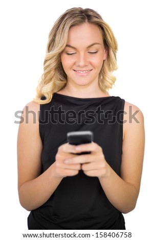 Cheerful gorgeous blonde in black dress on white background texting