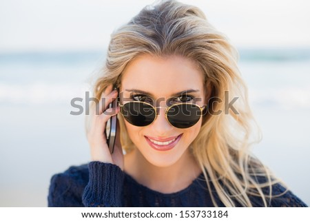 Cheerful gorgeous blonde on the phone looking over her sunglasses on a beautiful wild beach - stock photo