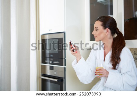 Cheerful gorgeous model holding smartphone standing in kitchen - stock photo