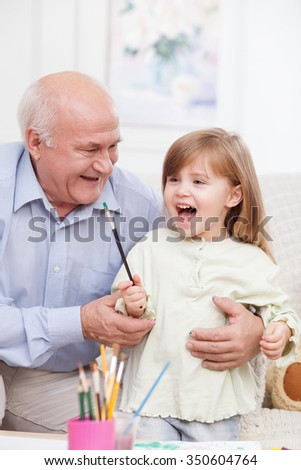 Cheerful grandfather is teaching his granddaughter to paint. They are sitting on couch and laughing. The girl is holding a paintbrush with joy - stock photo