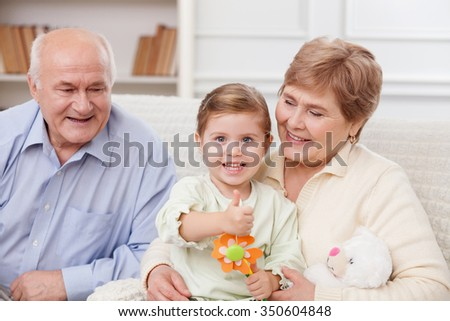 Cheerful grandmother and grandfather are taking care of their granddaughter. They are sitting on the couch and smiling. The girl is giving thumb up and holding pencils - stock photo