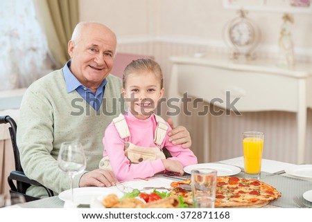 Cheerful grandparent has lunch with a child - stock photo