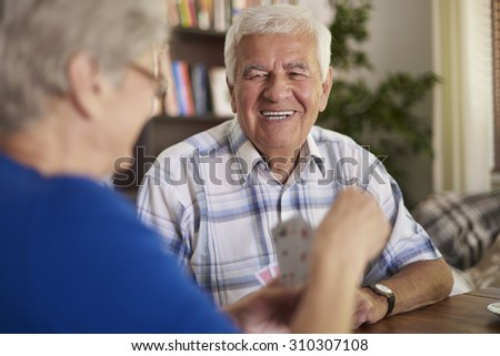 Cheerful grandparents playing cards in the afternoon  - stock photo