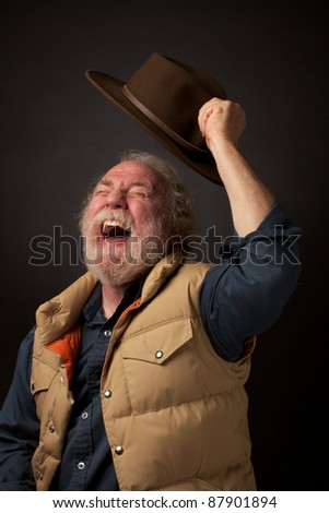 Cheerful gray bearded senior man shouts with joy and waves his hat in the air. He wears a down vest and blue denim shirt. Dark background and horizontal composition with copy space. - stock photo