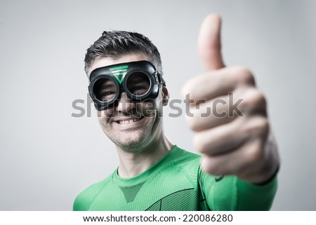 Cheerful green superhero thumbs up looking at camera.