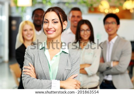 Cheerful group of co-workers standing in office - stock photo
