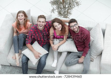 cheerful group of friends laugh ,sitting on the couch.