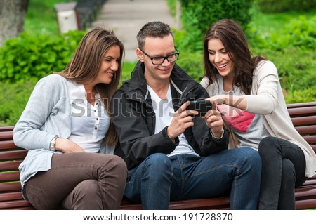 Cheerful group of friends, one man and two women sitting outdoor on a bench in park talking having fun laughing smiling happy watching something on mobile phone . - stock photo