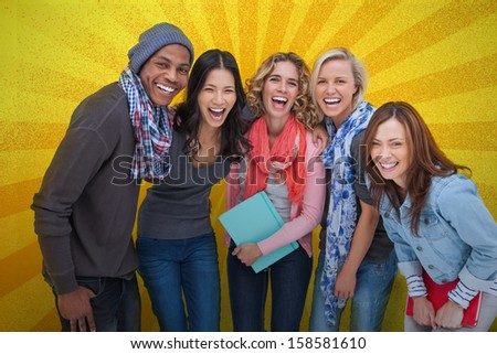 Cheerful group of friends posing together on yellow background - stock photo