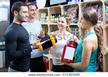 Cheerful group of young adults discussing bodybuilding supplements in gym. Focus on the blonde woman - stock photo