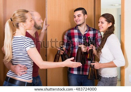 cheerful guests with bottles standing in doorway and smiling