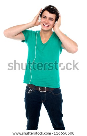 Cheerful guy enjoying loud music holding them tightly to ears - stock photo