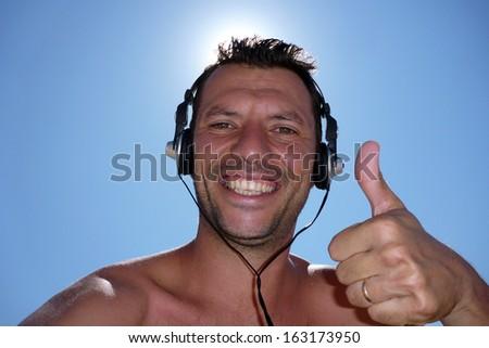 Cheerful guy enjoying loud music with headphones - stock photo