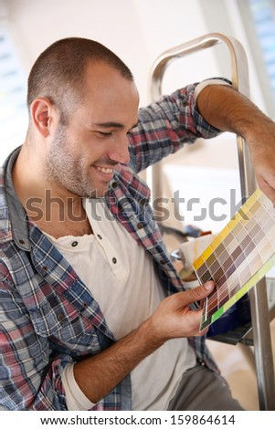 Cheerful guy in new apartment looking for paint colors - stock photo