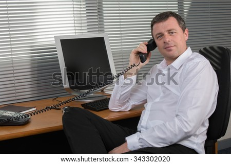 Cheerful guy sitting in front of desktop computer, talking to someone on the phone