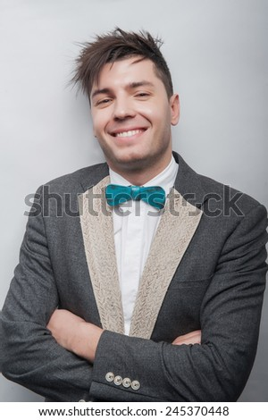 cheerful guy will be able to raise your mood. young attractive man smiles at you, in grey elegant tuxedo with a  blue bow-tie. on the white background - stock photo