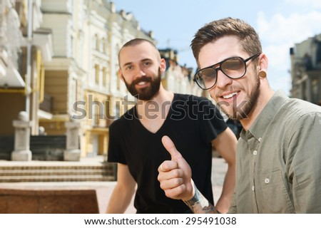 Cheerful guys are looking at the camera and smiling. One men with sunlasses is showing thumbs up positively - stock photo