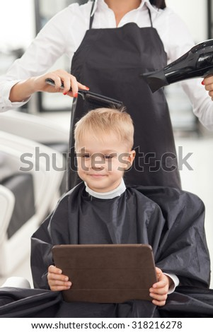 Cheerful hairstylist is drying hair of boy. The woman is holding a comb and hair-drier. The child is sitting and smiling. He is using a tablet - stock photo