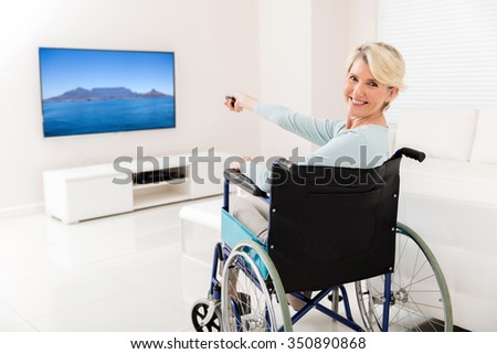 cheerful handicapped mid age woman watching tv at home - stock photo