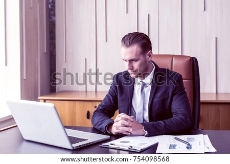 Cheerful Handsome businessman with laptop working in modern office. Happy Young successful caucasian manager glad because of sales-growth.