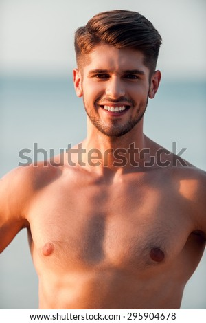 Cheerful handsome. Cheerful young muscular man looking at camera and smiling while standing outdoors
