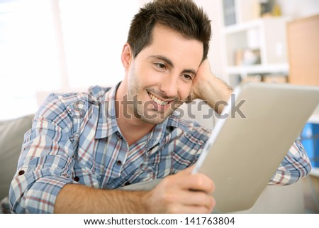 Cheerful handsome guy using tablet to read mail - stock photo