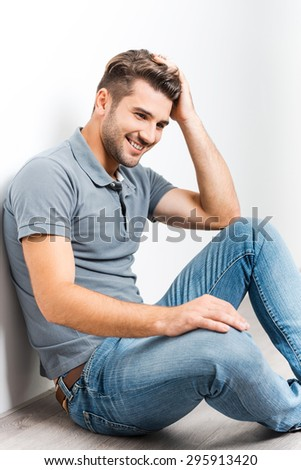 Cheerful handsome. Handsome young man holding hand in hair and smiling while sitting on the floor and leaning at the wall - stock photo