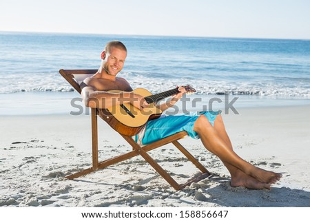 Cheerful handsome man playing guitar on the beach