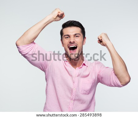 Cheerful handsome young businessman celebrating his success over gray background. Looking at camera - stock photo