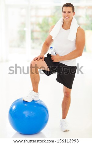 cheerful handsome young fitness man in gym