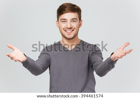 Cheerful handsome young man in grey pullover smiling and showing welcoming gesture over white background - stock photo