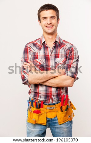 Cheerful handyman. Handsome young handyman with tool belt keeping arms crossed and smiling while standing against grey background - stock photo