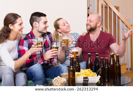 Cheerful happy adults drinking beer and laughing indoor. Selective focus - stock photo