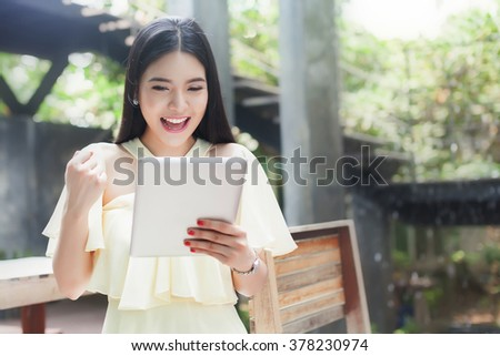 Cheerful happy Asian girl excited looking at touch pad tablet - stock photo