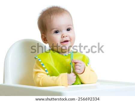 cheerful happy baby child sitting in chair with a spoon