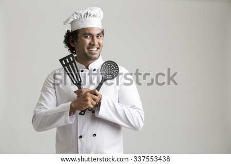 Cheerful happy chef holding kitchen utensil isolated on grey background - stock photo