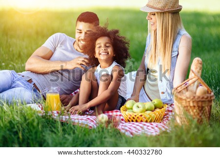Cheerful happy family picnicking on a beautiful day - stock photo