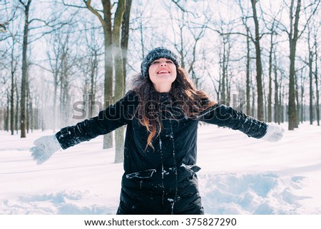 cheerful happy female enjoying the snow in winter park - stock photo