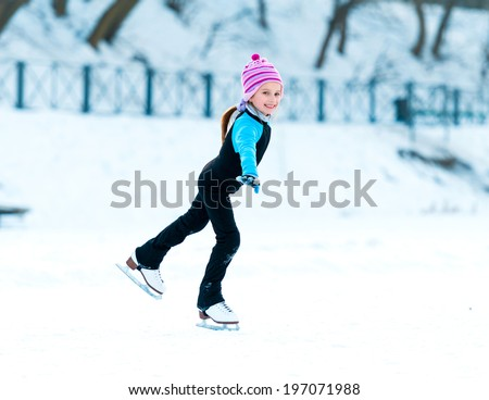 cheerful happy little girl in thermal suits skating in winter outdoors - stock photo