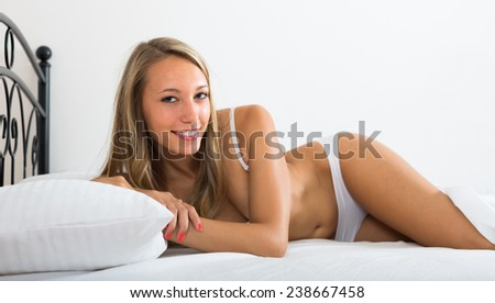Cheerful happy long-haired woman wearing underwear posing on bed at bedroom - stock photo
